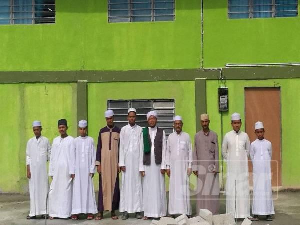 Mohd Nawawi (tengah) bersama sebahagian guru dan pelajar Pusat Pengajian Ulum Arabiah Kampung Sungai Darak.