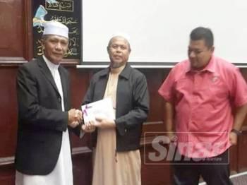 Mohd Zain menerima hadiah kemenangan yang disampaikan Imam Tua Masjid Mahmoodi, Bachok, Baharin Yusoff (tengah).
