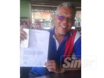 Rosman menunjukkan laporan polis kehilangan kereta di sebuah tempat letak kereta di sebuah pasar raya di Bukit Indah, Ahad lalu.