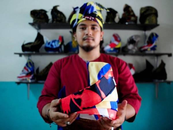 Pengarang Tanjak Mohd Zaim Hakimi Mohamad Zin, 25, menunjukkan tanjak yang dibuat menggunakan kain bercorak Jalur Gemilang yang ditempah oleh pelanggannya untuk digayakan sempena menyambut Hari Kebangsaan Ke-62 pada 31 Ogos nanti ketika ditemui di kediamannya di Puncak Alam Shah Alam. - Foto Bernama