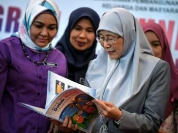 Dr Wan Azizah (kanan) melihat buku Modul Keibubapaan Datuk Nenek sempena Program Santuni Rakyat Peringkat Negeri Kedah anjuran Lembaga Penduduk dan Pembangunan Keluarga Negara (LPPKN) hari ini. - Foto Bernama