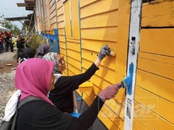 Warga PKNS bergotong royong mengecat salah sebuah rumah penerima dalam program ini di Jalan Pulai Kanchong Darat, Banting.
