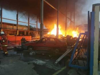 Anggota bomba berusaha memadamkan kebakaran.