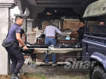 Anggota polis mengangkat mayat mangsa ke dalam trak untuk dibawa ke hospital.