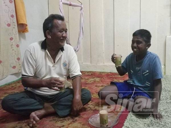 Mat Jatin (kiri) minum teh bersama Pararasan di rumahnya.