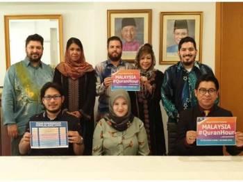 Khaeriah Zaehera (duduk tengah) bersama pegawai Kedutaan Besar Malaysia di Sepanyol memegang plakad Malaysia #QuranHour.