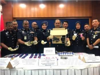 Abdullah (lima dari kanan) bersama anggota pegawai menunjukkan pistol dan dadah yang dirampas daripada empat suspek berkenaan.