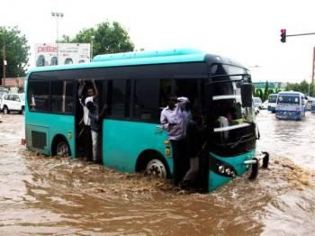 Sebuah bas melepasi sebatang jalan yang digenangi air di Khartoum.