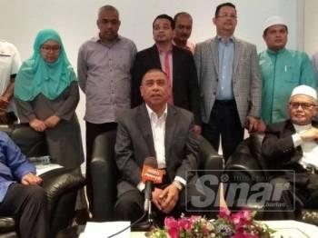 Saarani (duduk, kiri) bersama barisan ADUN pembangkang pada sidang akhbar mengenai isu pelepasan cukai kereta rasmi kerajaan negeri.