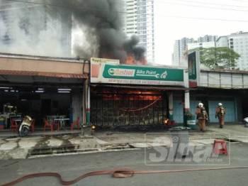 Anggota bomba berusaha memadamkan kebakaran di sebuah kedai motor di Jalan Lumba Kuda pagi tadi.