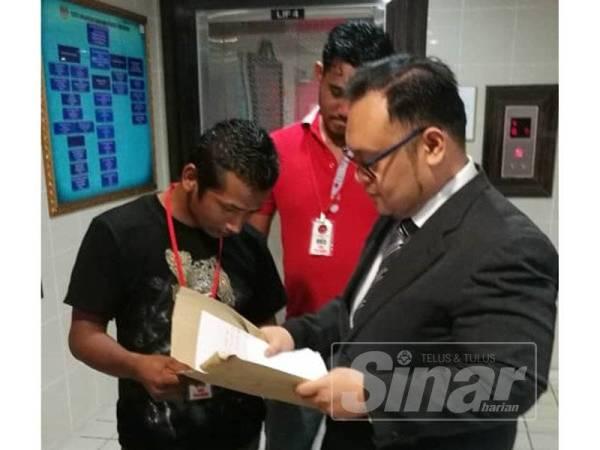 Md Zawawi (kiri) berbincang sesuatu dengan peguamnya, Mohd Hayatuddin (kanan) di luar kamar mahkamah.