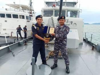 Pegawai Memerintah Kapal KM Marudu, Leftenan Komander Maritim Mohd Zahid Mohd Zahari (kiri) bersalaman dengan wakil APMM ketika menjalankan operasi bersama baru-baru ini.