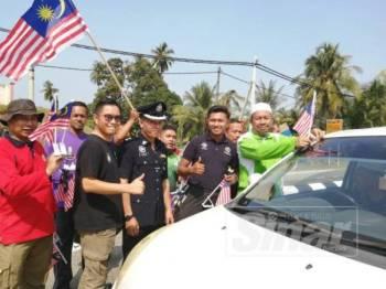 Maliaman (kanan) melekatkan Jalur Gemilang pada kenderaan pengguna jalan raya sewaktu Program Gotong-royong Merdeka di Ajil, Hulu Terengganu.
