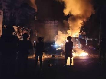 Anggota keselamatan Indonesia berkawal di sebuah lokasi menempatkan bangunan kerajaan di Jayapura yang dibakar perusuh dalam kejadian Khamis lalu.
