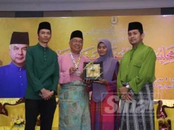 Muhammad Asri menunjukkan anugerah Tokoh Maal Hijrah Negeri Perak diterimanya sambil ditemani isteri, Haziana Abd Mutalib dan dua anak lelakinya, Ahmad Ammar, 33, (kanan) dan Aadil Ehsani, 27.