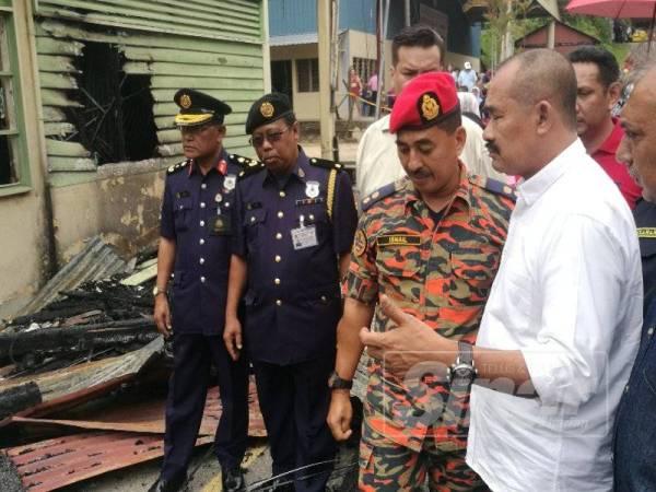 Abu Bakar diiringi Penolong Pengarah Bahagian Operasi Kebombaan Dan penyelamat JBPM Pahang, Ismail Abdul Ghani (tiga kiri) melawat lokasi kebakaran.