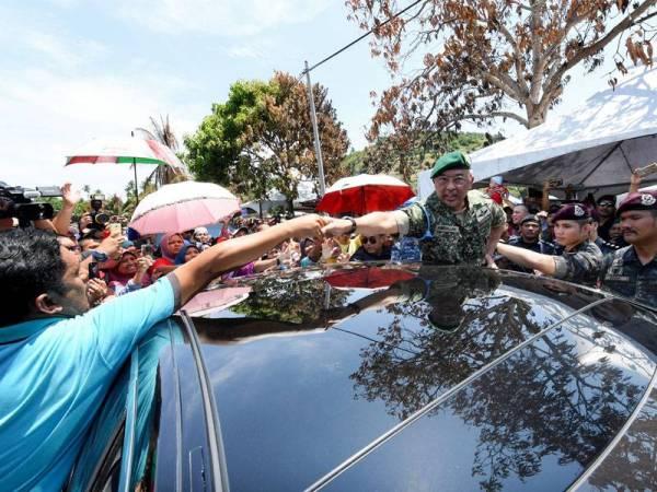 Al-Sultan Abdullah (tengah) berkenan bersalaman dengan penduduk sebelum berangkat pulang selepas melawat dan bertemu mangsa kebakaran rumah di Kampung Otentik, Tanjung Batu Keramat hari ini. - Foto Bernama