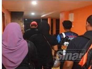 Sepasang kekasih (barisan tengah) yang ditahan dibawa keluar dari bilik disewa mereka untuk siasatan lanjut.