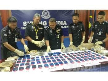 Aidi (tengah) menunjukkan sebahagian daripada pil kuda yang dirampas dalam serbuan kelmarin. Ada bersama, Ketua JSJN Terengganu, Superintendan Roslan Tahir (dua dari kiri).