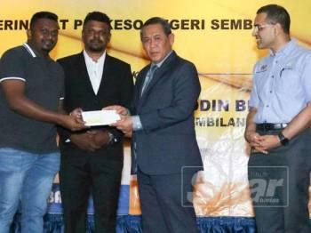 Aminuddin (dua dari kanan) menyampaikan cek kepada salah seorang pencarum. Turut kelihatan Mohammed Azman (kanan).