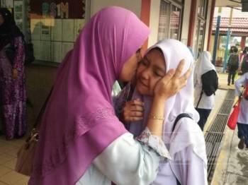 Nor Amidah mencium anaknya Izzatul Aliyah sebelum peperiksaan UPSR bermula di SK Bandar Pontian, hari ini.
