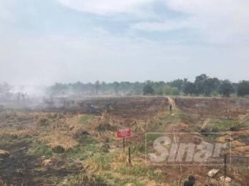 Tanah ladang tanah gambut di Jalan Johor-Pontian yang terbakar sejak semalam.