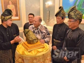 Tuanku Syed Sirajuddin mendengar penerangan yang disampaikan Mohd Nazim mengenai tengkolok Putra Julang Darjat di Balai Menghadap Biru Istana Arau semalam.