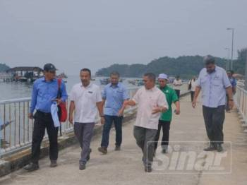 Azman (dua dari kanan) bersama Zawawi dan pegawai agensi terbabit ketika melawat Pulau Redang.
