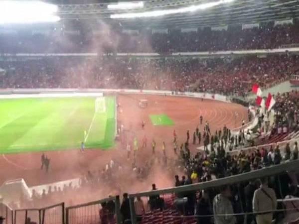 Keadaan cemas ketika penyokong Malaysia dihujani botol dan batu di Stadium Utama Gelora Bung Karno pada Khamis. - Foto Astro Awani