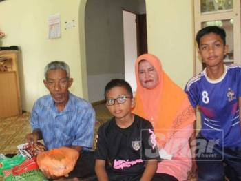 Syukri (tengah) bersama bapanya, Johan dan ibunya Samsiah di rumah mereka di Kampung Tanjung Piai, Serkat.