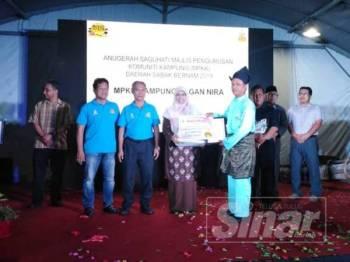 Rodziah menyerahkan anugerah kepada salah seorang Pengerusi Majlis Pengurusan Komuniti Kampung (MPKK) sempena Mini Ekspo Usahawan Selangor dan Karnival Sayangi Desa 2019 Daerah Sabak Bernam di Sabak Sentral Mall semalam.