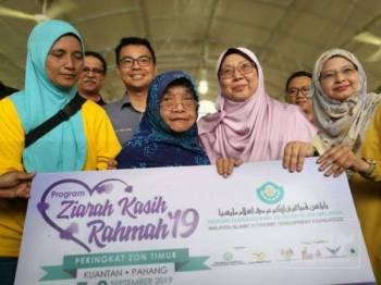 Fuziah (dua dari kanan) menyampaikan simbolik sumbangan membaik pulih rumah asnaf kepada salah seorang penerima sempena program tersebut.