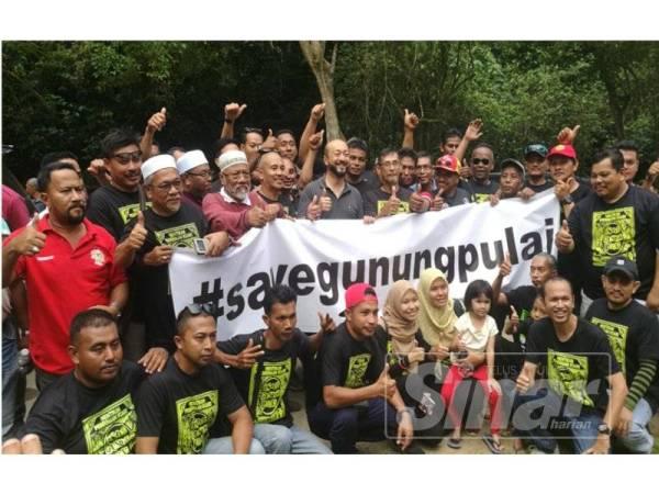 Mukhriz bergambar bersama penduduk sambil memegang kain rentang Save Gunung Pulai.