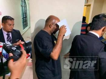 Abdul Malik (tengah) ketika keluar dari kamar perbicaraan di Mahkamah Majistret Johor Bahru hari ini.