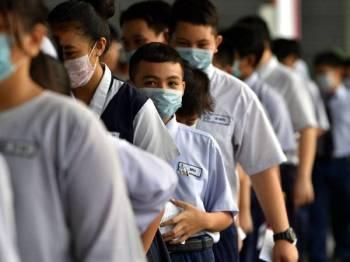 Murid darjah enam menduduki peperiksaan dengan menggunakan topeng hidung dan mulut di Sekolah Kebangsaan Jalan Ong Tiang Swee Kuching, semalam. - Foto BERNAMA