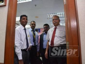 Ramasamy (kanan) dan Satees (dua dari kanan) dilihat keluar dari pejabat selepas diambil keterangan oleh dua pegawai polis tadi.