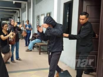 Suspek yang merupakan Hakim Mahkamah Rendah Syariah dibawa keluar selepas mendapat perintah reman.