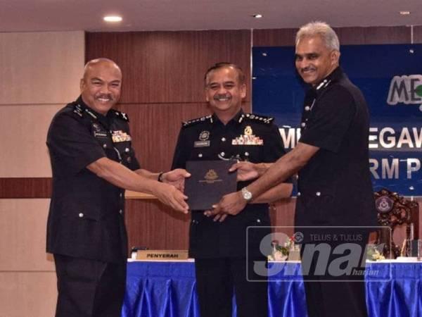 Razarudin (tengah) menyaksikan serah terima tugas jawatan Ketua JPJKK Perak, antara Mohamad Laham (kiri) dan G S Suresh Kumar.