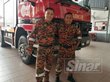 Marzuki (kanan) bersama rakan sekerja, Mohd Afendi.