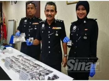 Adzli (tengah) menunjukkan dadah dirampas yang dianggarkan seberat 1.2 kilogram dan bernilai kira-kira RM36,690.