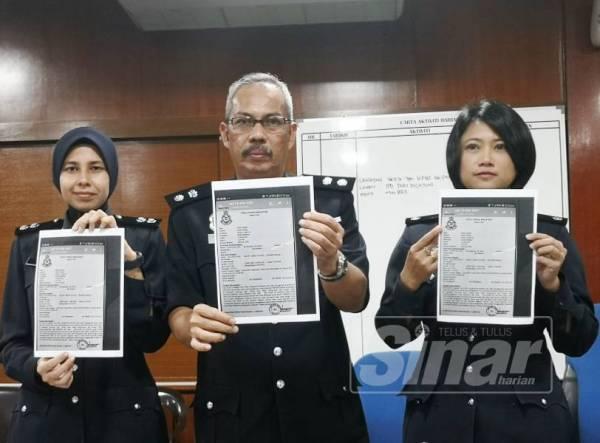 Aidi Sham (tengah) menunjukkan laporan polis palsu yang digunakan sindiket Macau Scam memperdaya seorang warga emas di Port Dickson hari ini.
