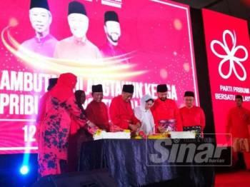 Dr Mahathir ditemani Tun Dr Siti Hasmah Mohd Ali memotong pulut kuning pada Majlis Sambutan Ulang Tahun Ketiga Bersatu malam tadi.