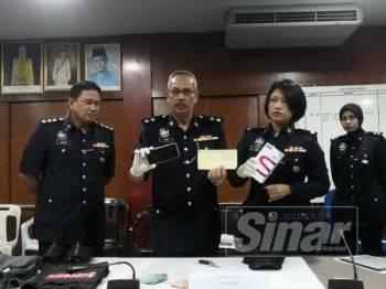 Aidi Sham (dua dari kiri) menunjukkan telefon bimbit yang dibeli suspek menggunakan duit hasil samun.