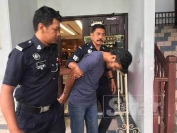 Tertuduh ketika dibawa keluar dari Mahkamah Sesyen Ayer Keroh selepas didakwa melakukan amang seksual terhadap anak tirinya.