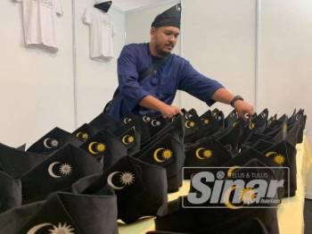Alif menjual tanjak dengan harga RM30 pelbagai saiz di gerai jualan Himpunan Penyatuan Ummah di Pusat Dagangan Dunia Putra (PWTC), Kuala Lumpur hari ini.