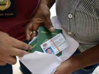 Pegawai Imigresen menunjukkan sebahagian dokumen pasport dan pas lawatan kerja sementara warga asing dipalsukan sindiket 'Mama Bangla' semalam.
