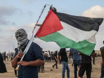 Seorang penunjuk perasaan memegang bendera Palestin ketika pertempuran dengan tentera Israel di sepanjang sempadan Khan Yunis. - Foto AFP