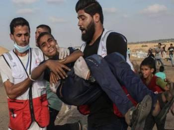 Seorang kanak-kanak Palestin diberi bantuan selepas terkena peluru getah dilepaskan tentera Israel semasa bantahan di timur Khan Yunis.