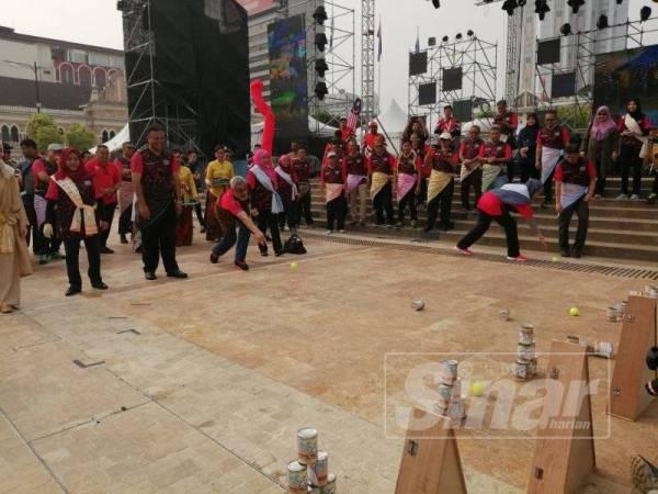 Khalid mencuba permainan baling tin pada Festival Permainan Malaysia @Kuala Lumpur di Dataran Merdeka hari ini.