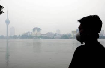 Seorang lelaki memakai penutup hidung dan mulut ketika melihat bandar Kuantan yang berkabus akibat jerebu pada tinjauan hari ini. Foto: Bernama